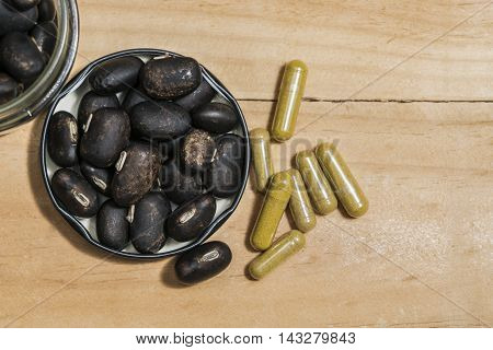 The seeds of Velvet bean or Mucuna pruriens and Pill capsules that contain herbal medicine powder have been used for traditional medicine selective focused on wooden background with copy space