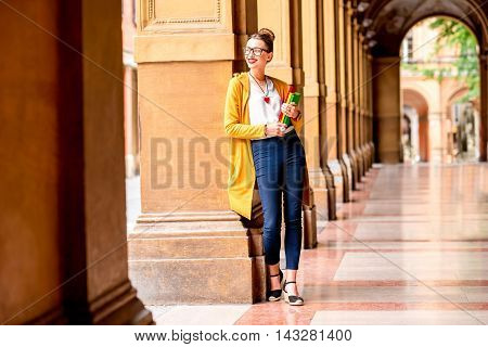 Young female student dressed casually standing with books in the famous arched galleries in Bologna city in Italy. Bologna is student city and home to the oldest university in the world