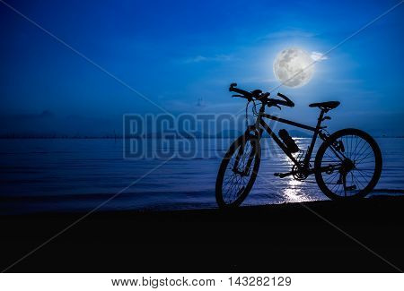 Silhouette of bicycle on the beach against bright full moon over the sea blue sky background. Outdoors. The moon were NOT furnished by NASA.