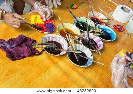 Women hands paint on tie dye fabric.