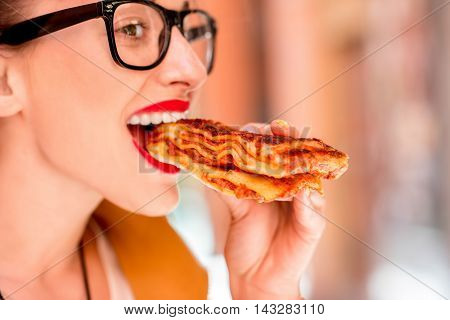 Young woman eating lasagna with bolognese outdoors on the street in Bologna city in Italy. Lasagna bolognese was invented in Bologna city. Soft focus with small depth of field