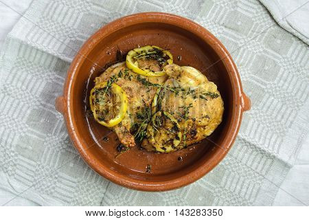 Roasted chicken with thyme and lemon in a clay pot