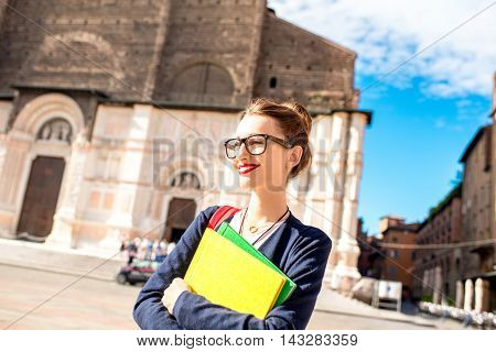 Young female student with books on the central square in Bologna city in Italy. Bologna is a student city and home to the oldest university in the world