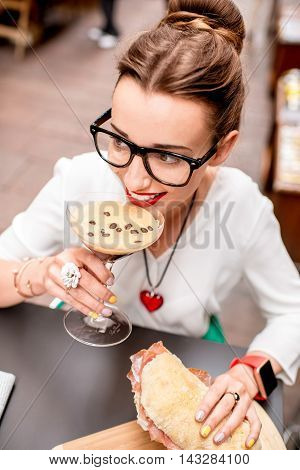 Young woman with shakerato coffee drink and panini with prosciutto outdoor.