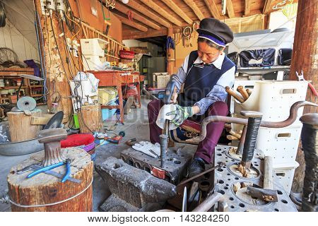 Heqing, China - March 16, 2016: Bayi Woman Making A Silver Pot. Heqing Is Famous For The Artigianal