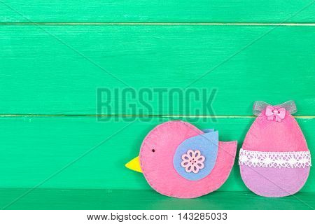 Decorative felt bird and egg on the wooden background with copy space for text. Easter background