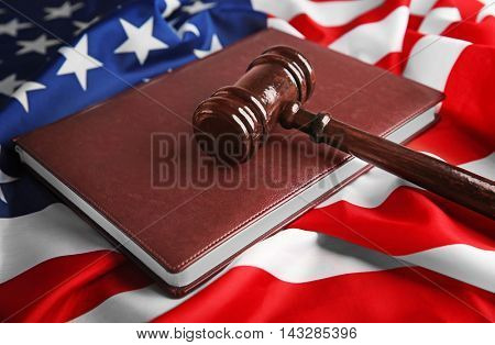 Judge gavel and book on American flag, closeup