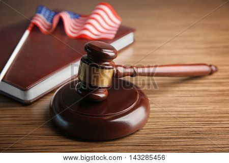Judge gavel with book and American flag on table