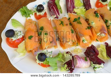 Wonderful and tasty smoked salmon rolls with salad tomatoes olive and cheese