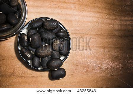 The seeds of Velvet bean or Mucuna pruriens have been used for traditional medicine selective focused on wooden background with copy space