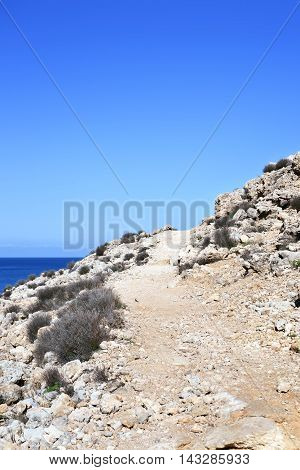 Dry cliff coast with footpath and blue sky with copy space.