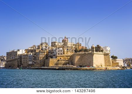 Malta - The ancient walls of Senglea and Gardjola Gardens shot from Valletta on a sunny day with clear blue sky