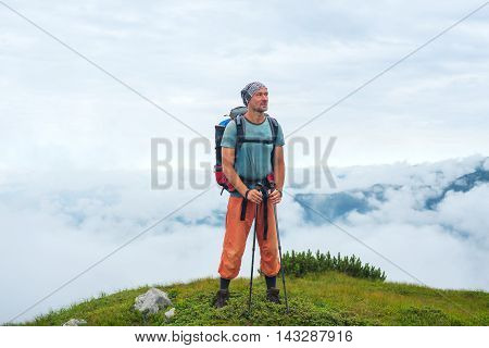 Smiling hiker with a backpack stands above the clouds on the top of the mountain. Beautiful day in the Carpathian mountains.