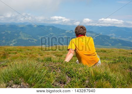 Hiker man sitting on a alpine . Back view. Wonderful evening in the mountains.