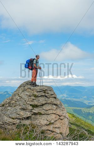 Hiker with a backpack stands on a rock against the blue sky and clouds. Beautiful day in the Carpathian mountains.