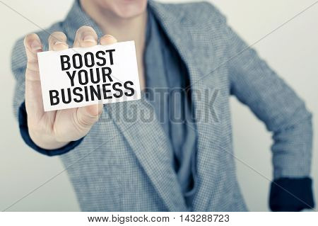 Hand holding paper with boost your business note
