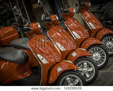 May 24, 2016 - Paris, France: Motor scooters are a popular and economical means of transportation on the busy streets of Paris. These shiny new red motor scooters are for sale at a Vespa dealership in Paris.
