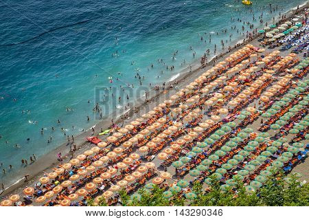 Aerial photography of tourists playing and taking sunbath on a sandy beach in Positano Italy
