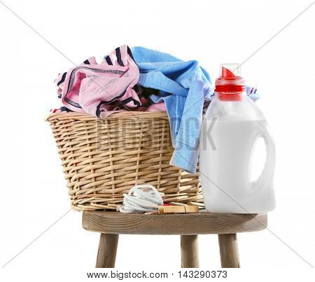 Wicker basket with baby laundry and cleanser on white background