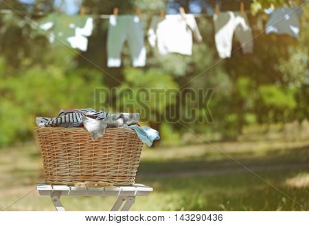 Wicker basket with baby laundry on blurred clothesline background