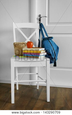 Schoolbag with lunch on stool