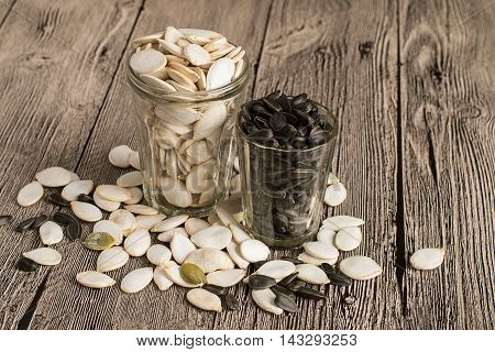 Beakers with pumpkin seeds and sunflower on gray wooden table.