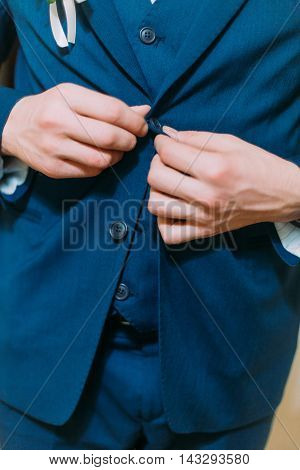 Elegant young man dressing blue jacket as part of his luxurios suit for special event.