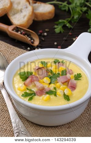 Puree soup of corn with slices of fried bacon with parsley