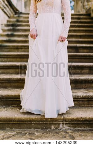 Charming girl in long white dress going down by antique stone stairs.