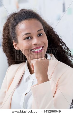 Smiling female employee in the office wearing a jacket
