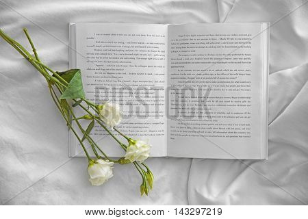Opened book and beautiful flower on white crumpled sheet