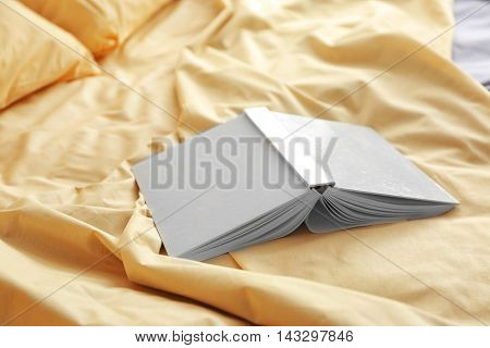 Open upside book on crumpled bed