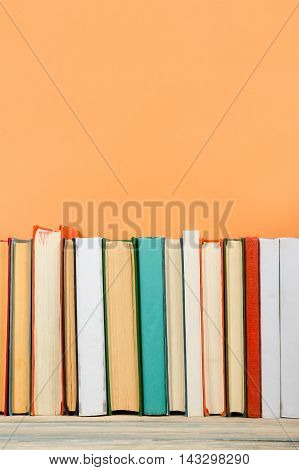 Colorful composition with vintage old hardback books, diary on wooden deck table and orange background. Books stacking. Back to school. Copy Space. Education background