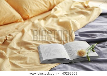 Opened book and beautiful flower on crumpled bed in room