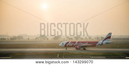BANGKOK THAILAND - JAN 23 2015: Airliner Air-Asia Airbus A320 landing at Bangkok airport on Jan 23 2015. Air Asia company is the largest low cost airlines in Asia.