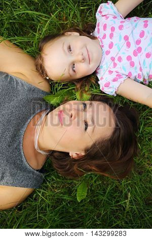 Little cute girl and her mother lie on grass and look up in park