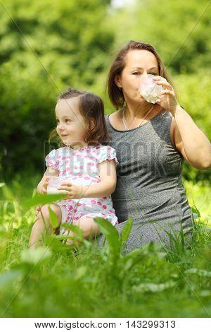 Little girl holds milk and her mother drinks milk in sunny park