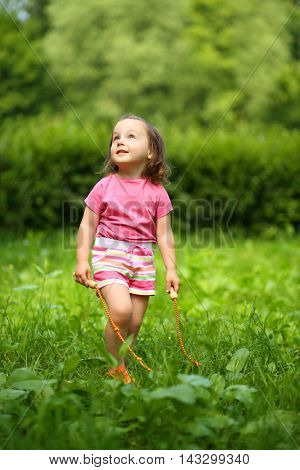 Little cute girl with skipping rope looks up in summer sunny garden