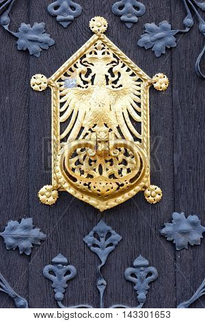 Close up of a black traditional German doorway with golden doorknob accents.