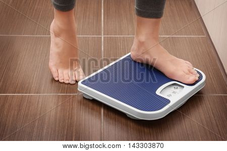 Female bare feet standing on a scales in bathroom