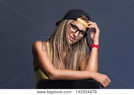 Portrait of attractive blonde girl in glasses and cap smiling at camera on grey background.Studio shot.