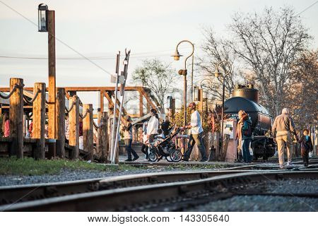 Sacramento, USA - Feburary 20, 2016: People walking across railroad tracks during sunset in capitol city of California