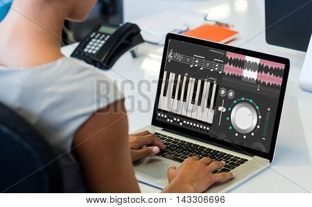 Music app against woman working on laptop while sitting on chair