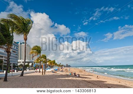 Fort Lauderdale Fl USA - November 27 2011: View of public Fort Lauderdale beach with people on autumn break vacations enjoying the warm sunny weather on the sand and in the Atlantic ocean.