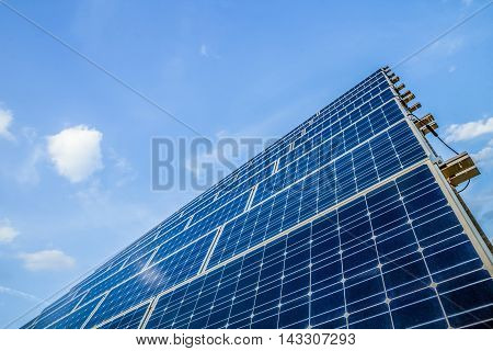Closeup of blue photovoltaic solar panels and sky background