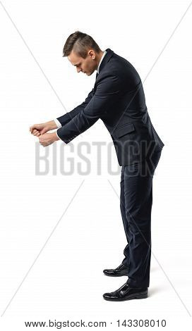 Side view of a businessman looking downwards and holding something isolated on white background. Business staff. Office clothes. Body language.
