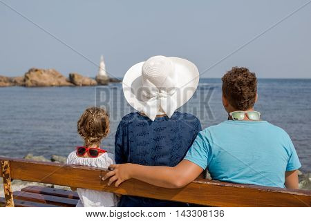 Back view of seated family on a bench at the beach