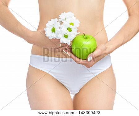 The female body the hands holding a daisy at the waist on a white background