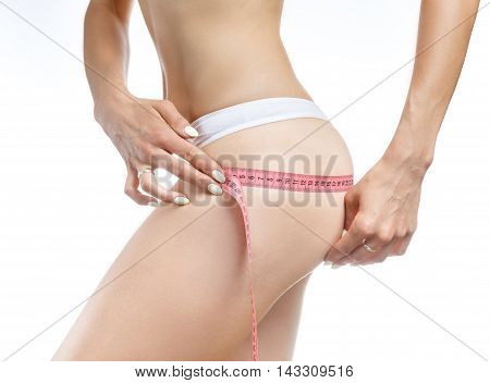Woman holding red meter measuring perfect shape of her beautiful body on a white background