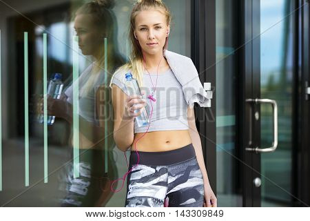 Smiling blonde woman in sportswear takes a break after workout. Stands in urban city environment in tights and crop top. Reflection in window.